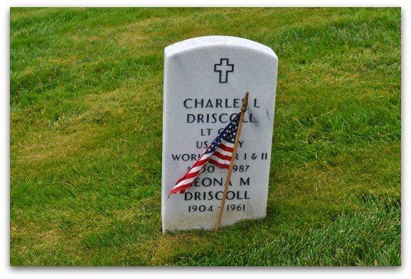 A US flag in front of a gravestone during the annual Memorial Day event
