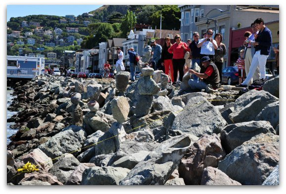 Visitors watching a local artists balance rocks in Sausalito.